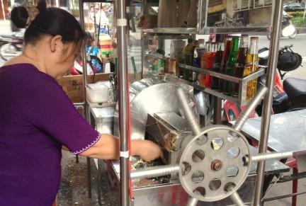 Woman produces sugar cane juice