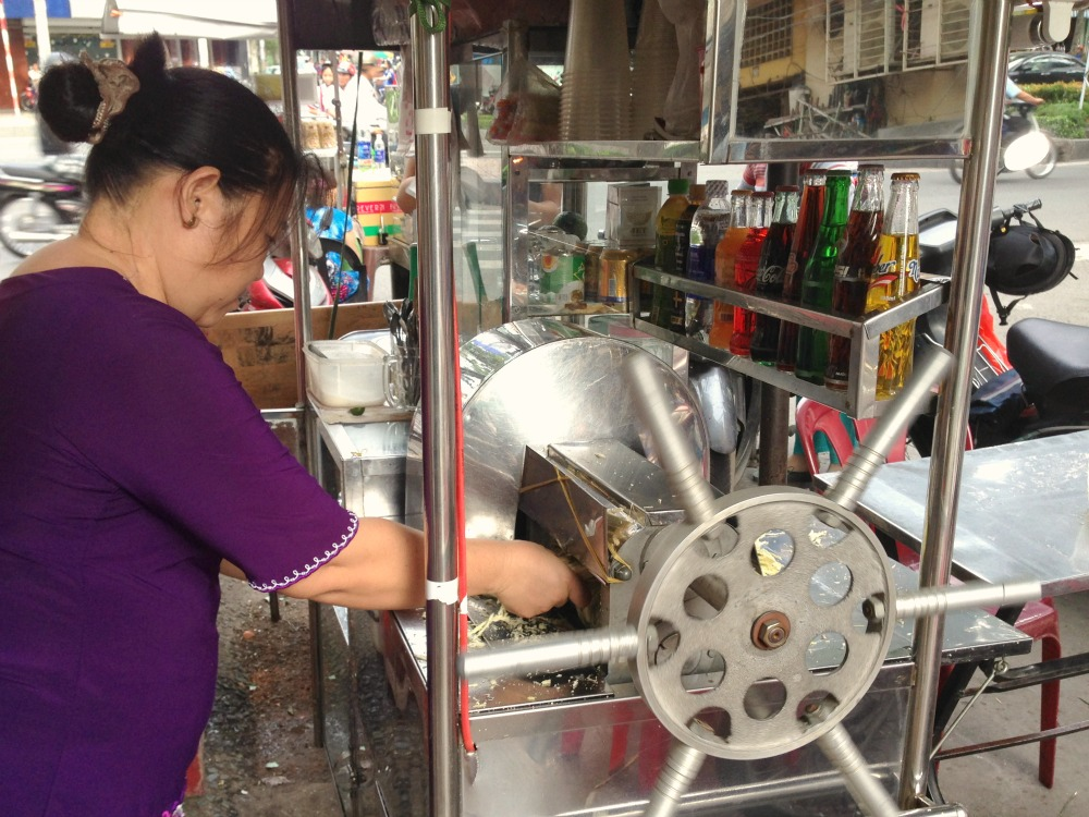 Woman produces sugar cane juice